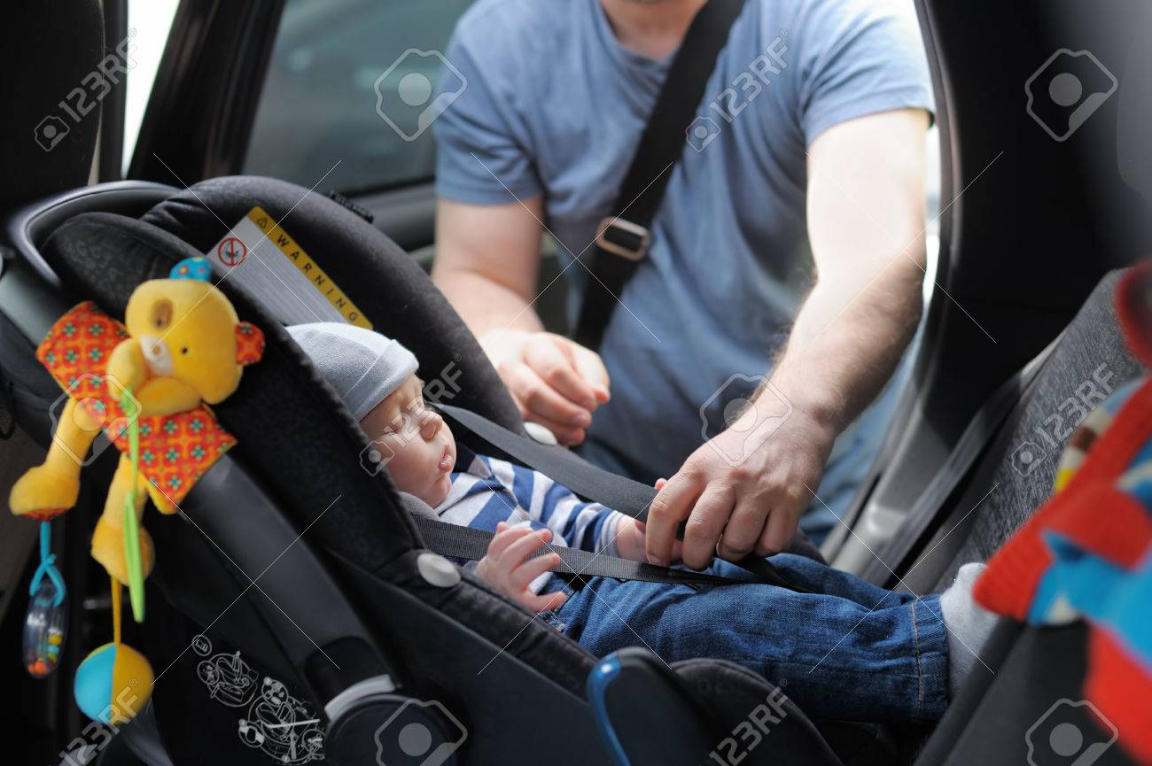 Father fasten his little son in car seat - 35564889