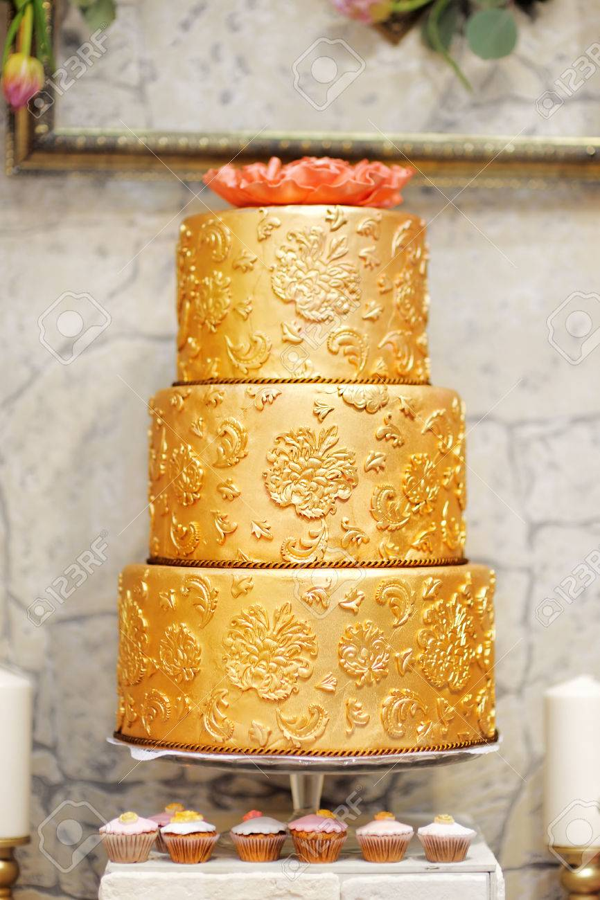 Sweet table with big golden cake for wedding party - 37616317