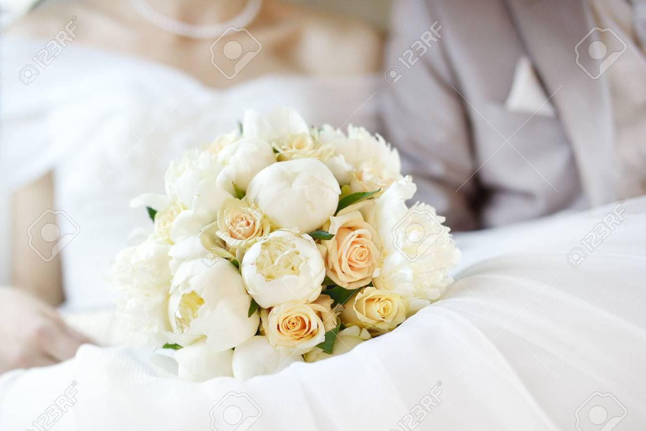 Wedding flowers bouquet with newlywed couple on background - 37616347