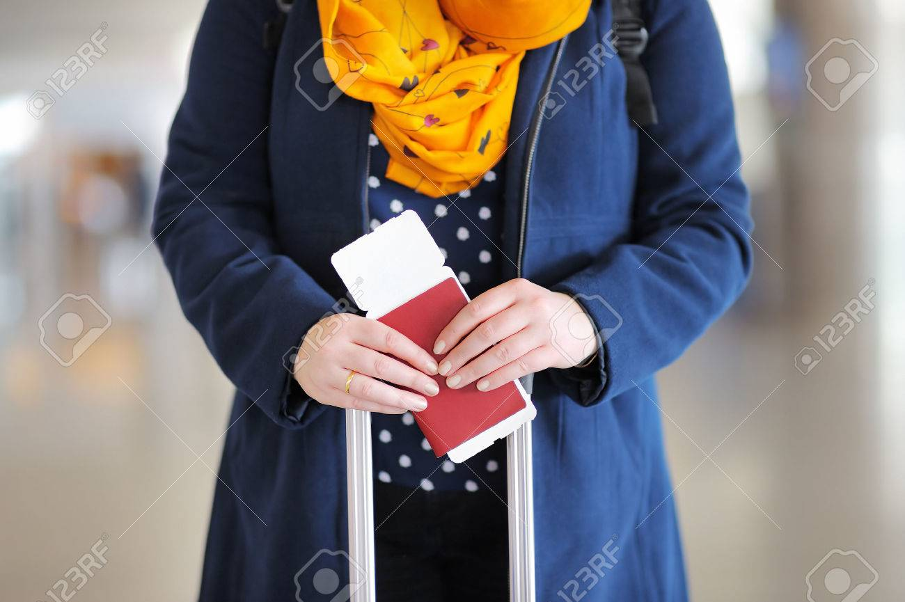 Close up photo of woman holding passport and boarding pass at the airport - 38719308