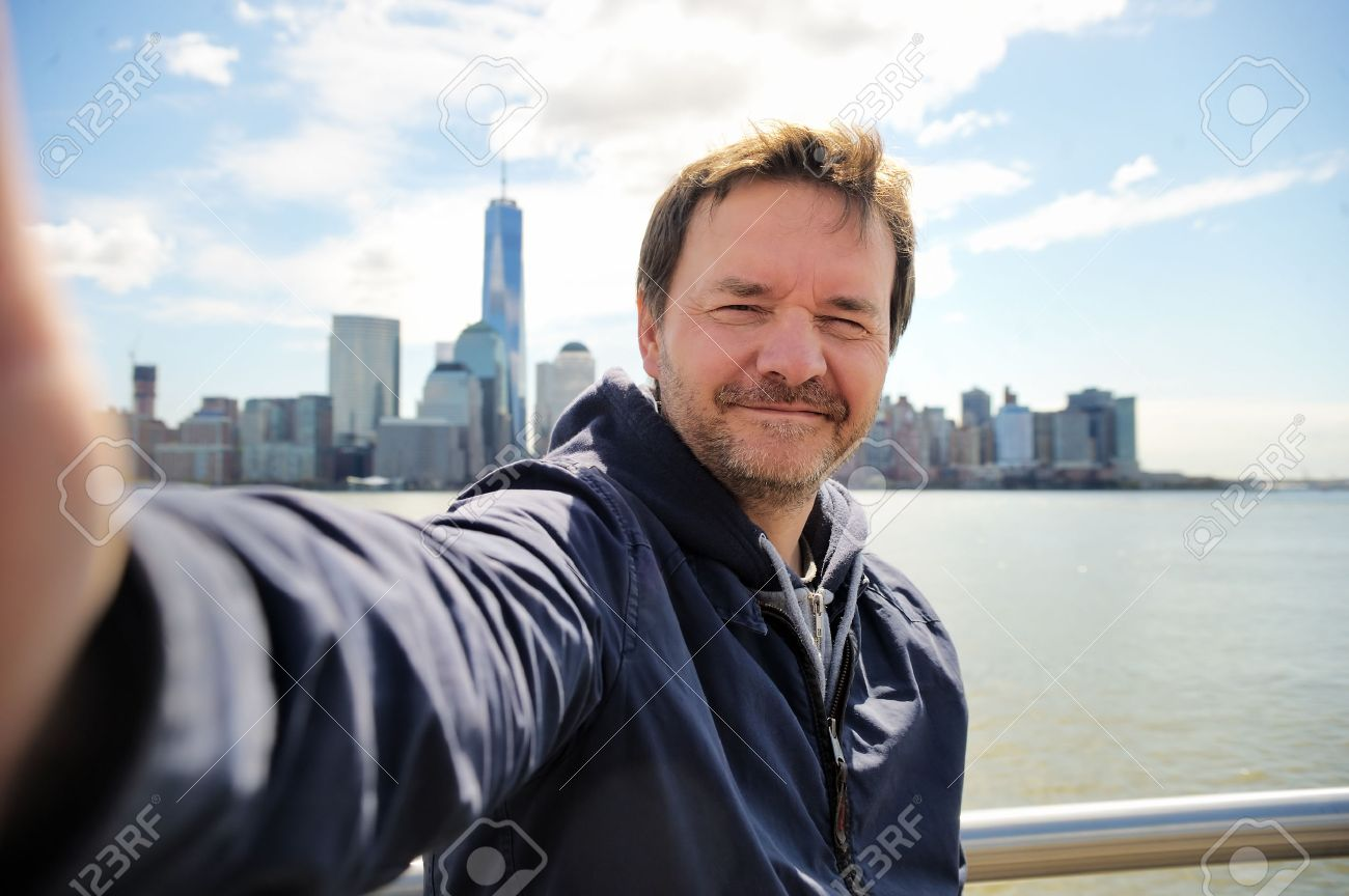Middle age man taking a self portrait (selfie) with Manhattan skyscrapers in New York City - 39594418