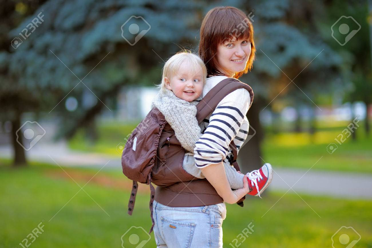 Happy young mother with her toddler child in a baby carrier - 41973657