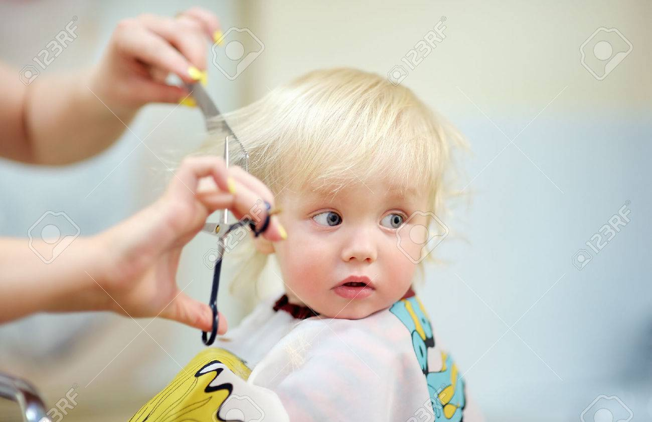 Close up portrait of toddler child getting his first haircut - 42194928