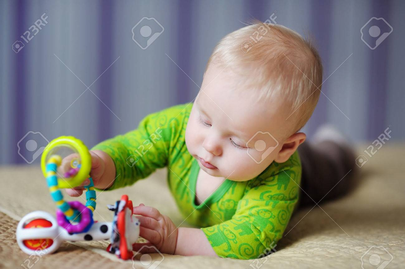 Six month old baby play with bright toys - 42772487