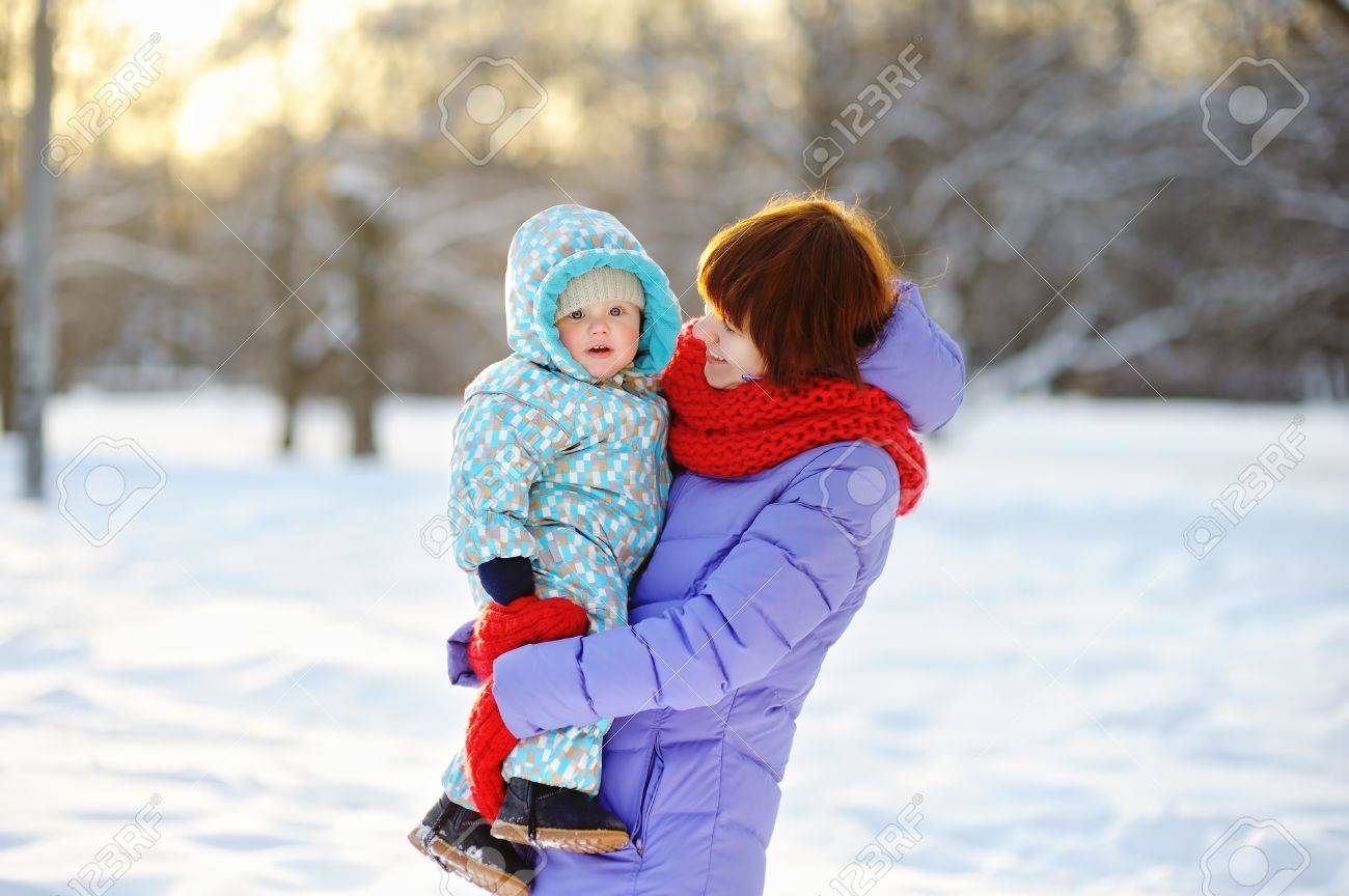 Young woman with her toddler boy at the winter park - 44784262