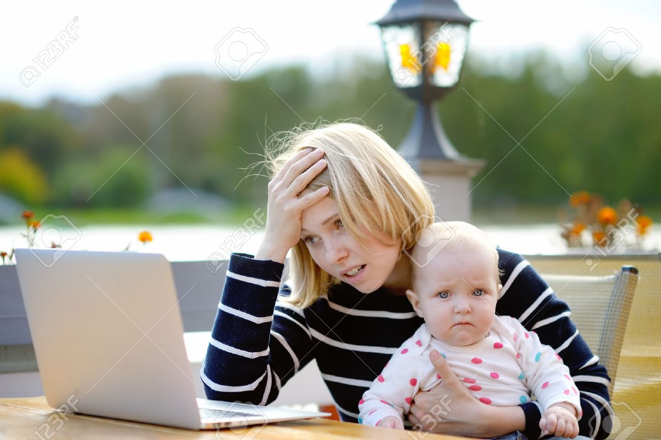 Tired young mother working oh her laptop and holding 6-month daughter - 47226618