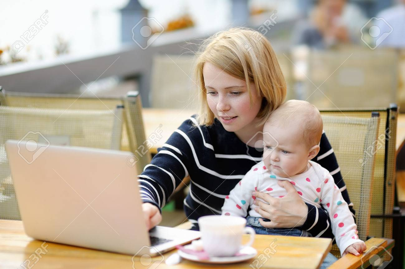 Young mother with her adorable baby girl working or studying on her laptop in outdoor cafe - 47403332