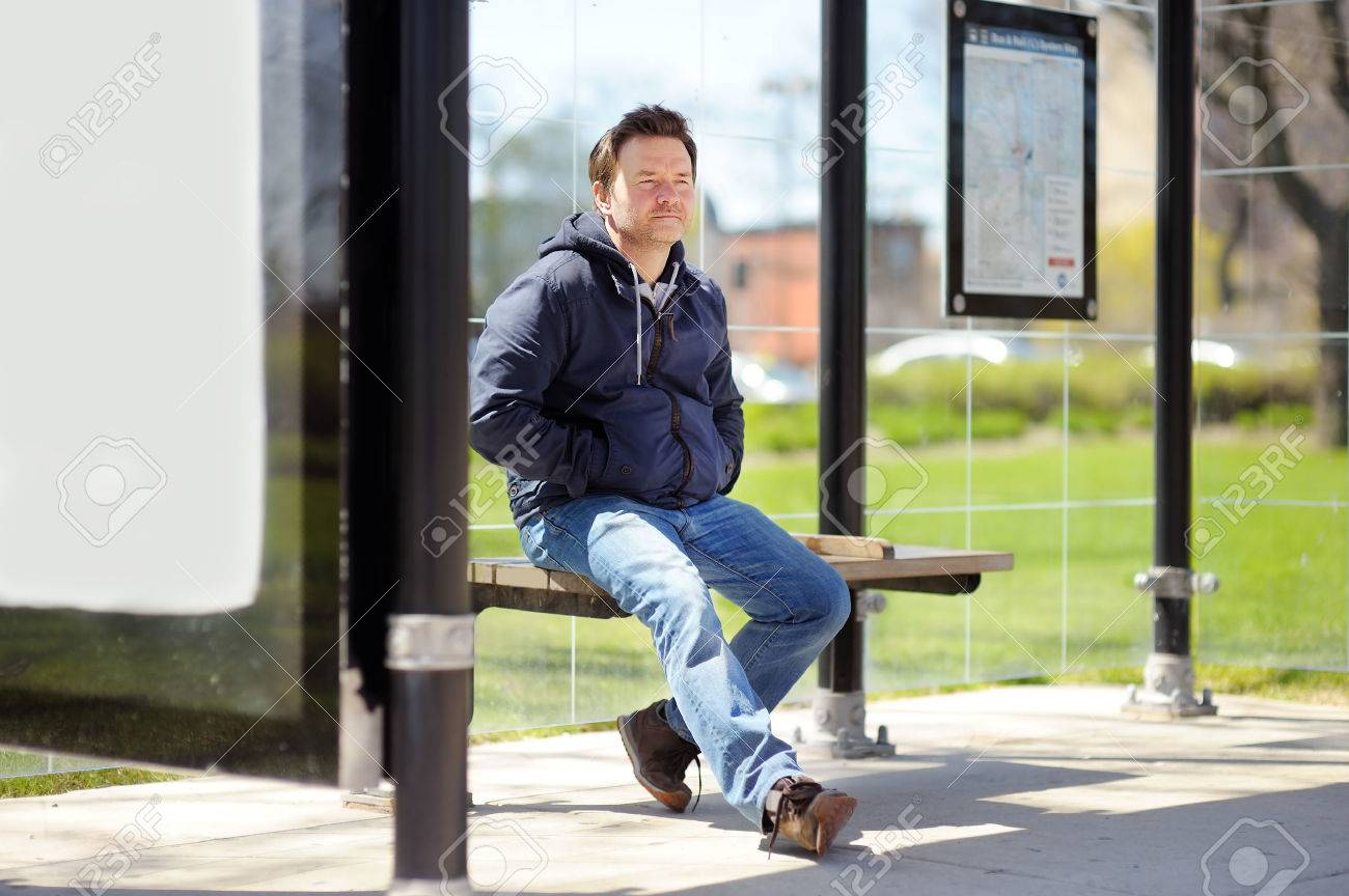 Middle age man sitting on bench on bus stop - 53289699