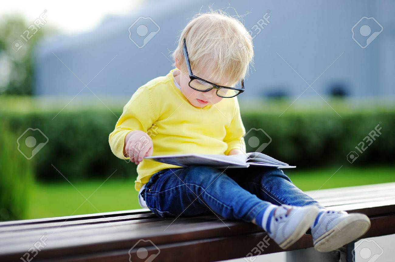 Cute toddler boy reading a book outdoors on warm summer day. Back to school concept - 59396937