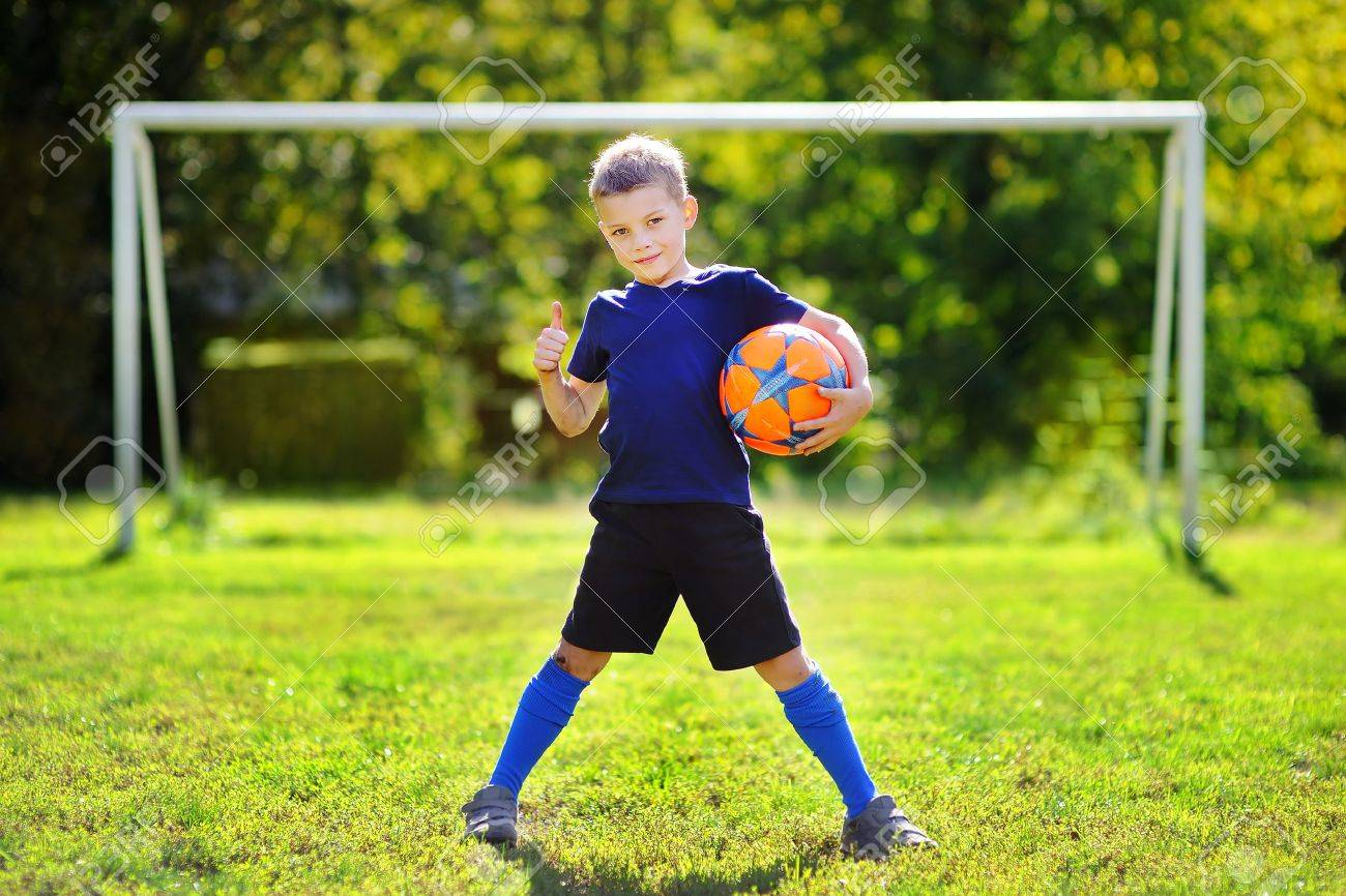 Little boy having fun playing a soccer game on sunny summer day - 62388313
