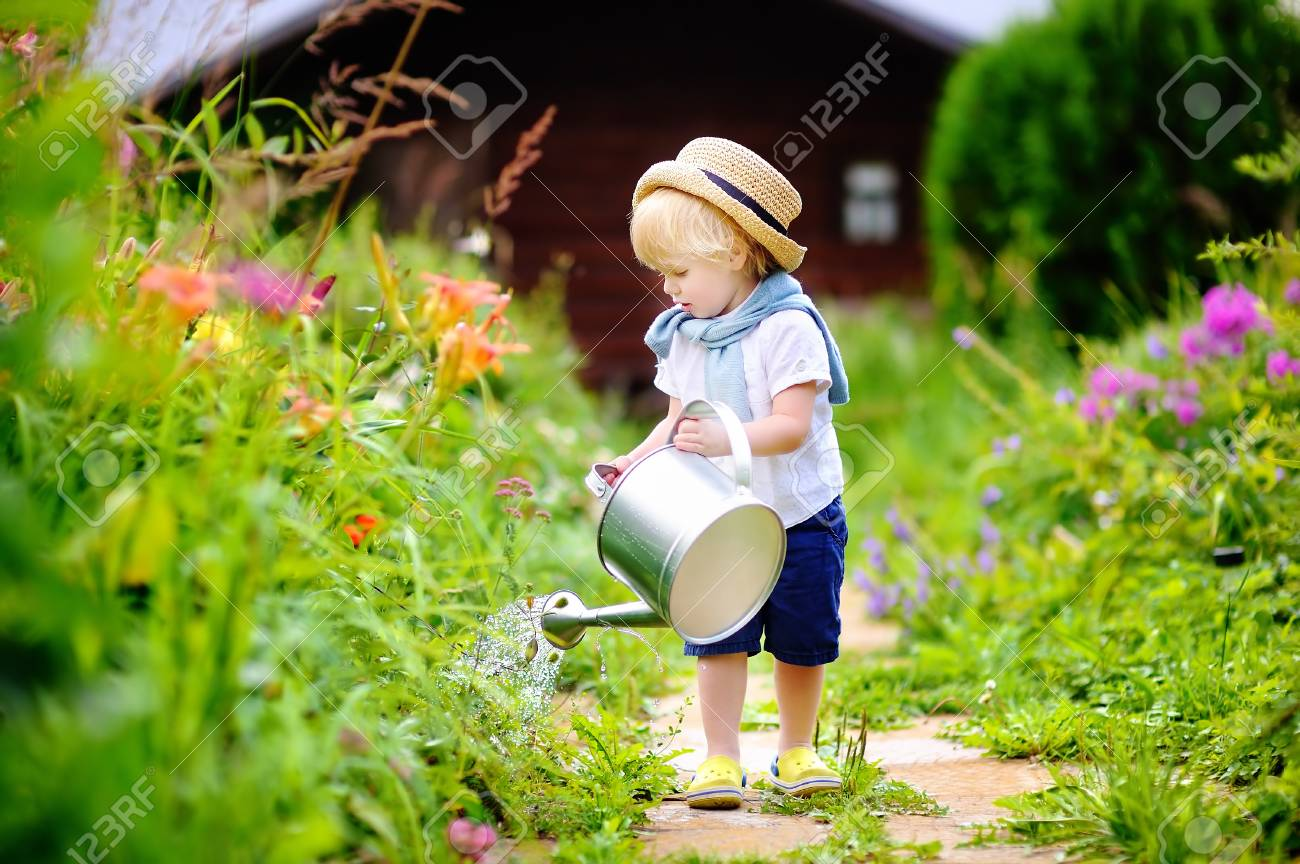 Cute toddler boy in straw hat watering plants in the garden at summer sunny  day Stock c28671df856d