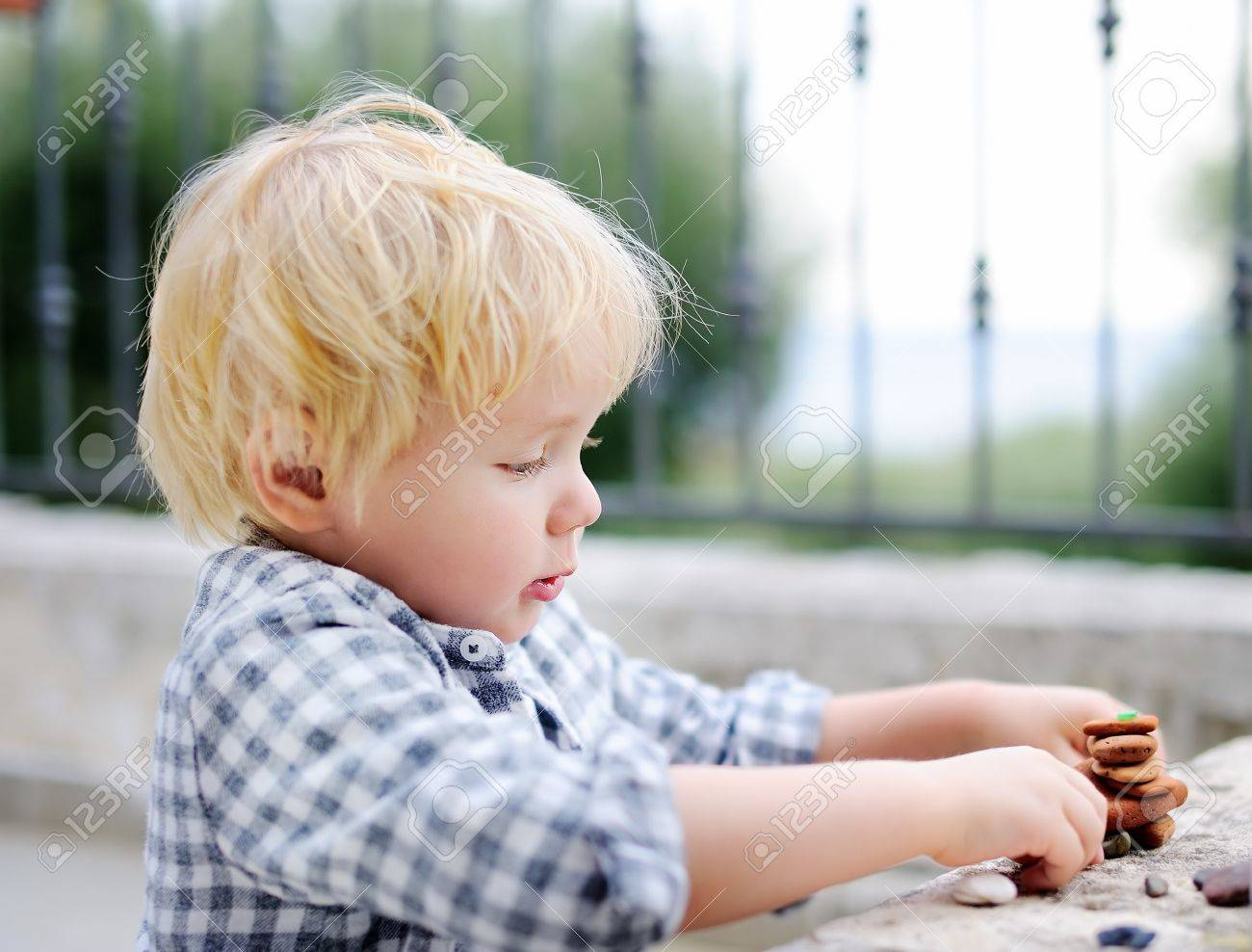ab8ff54caad9 Cute blonde little boy playing with little stones outdoors. Toddler child  builds tower Stock Photo