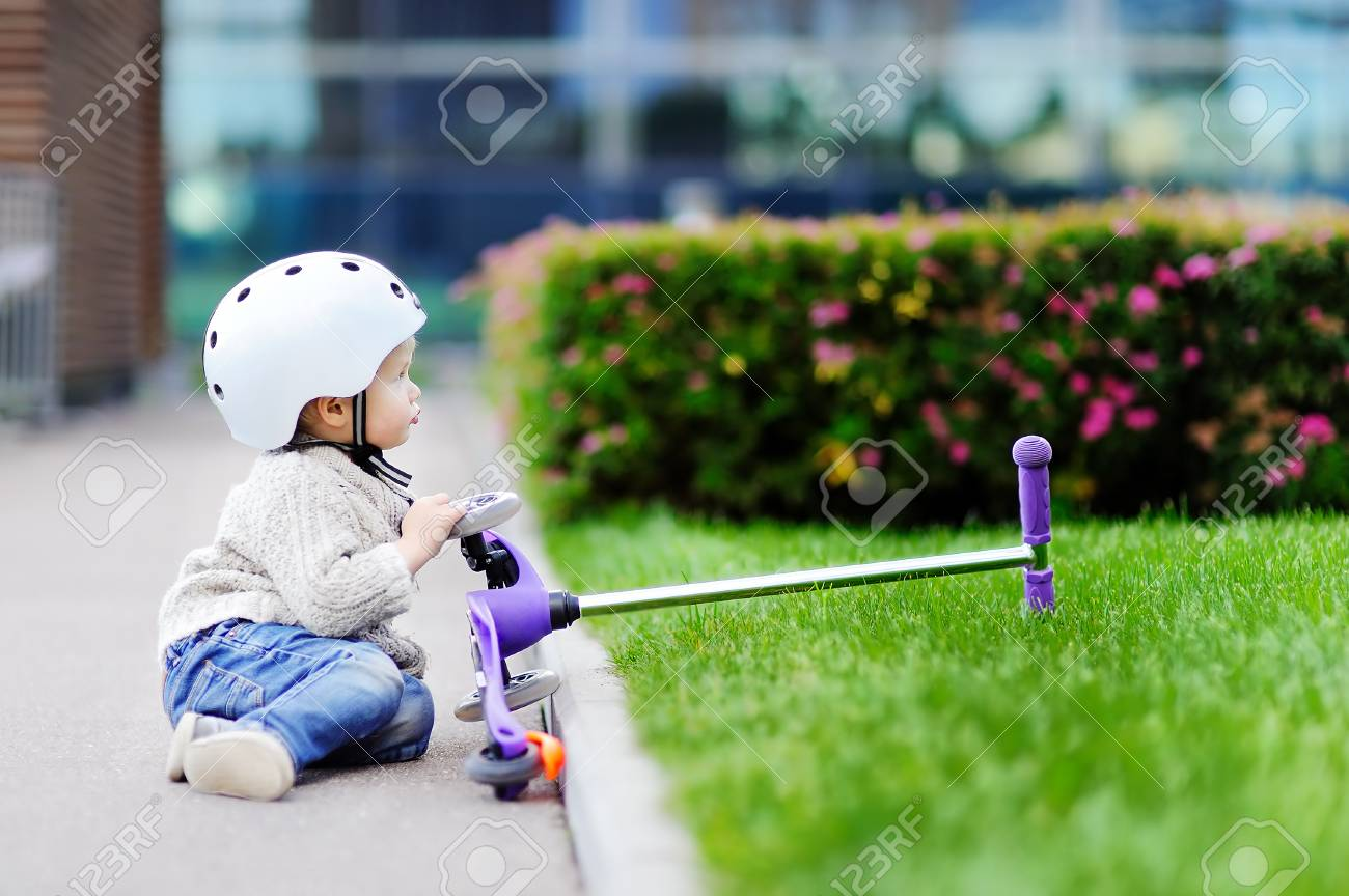 403bd88963629 Toddler Boy In Safety Helmet Learning To Ride Scooter Stock Photo ...