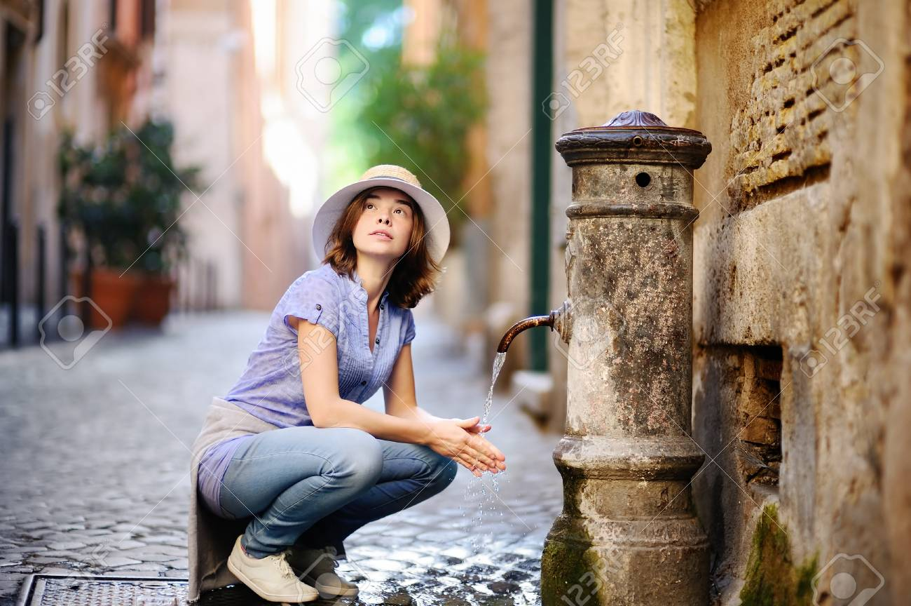 Young woman washing hands in a city fountain. Young woman drinking clean water from the fountain in Rome, Italy - 80153934