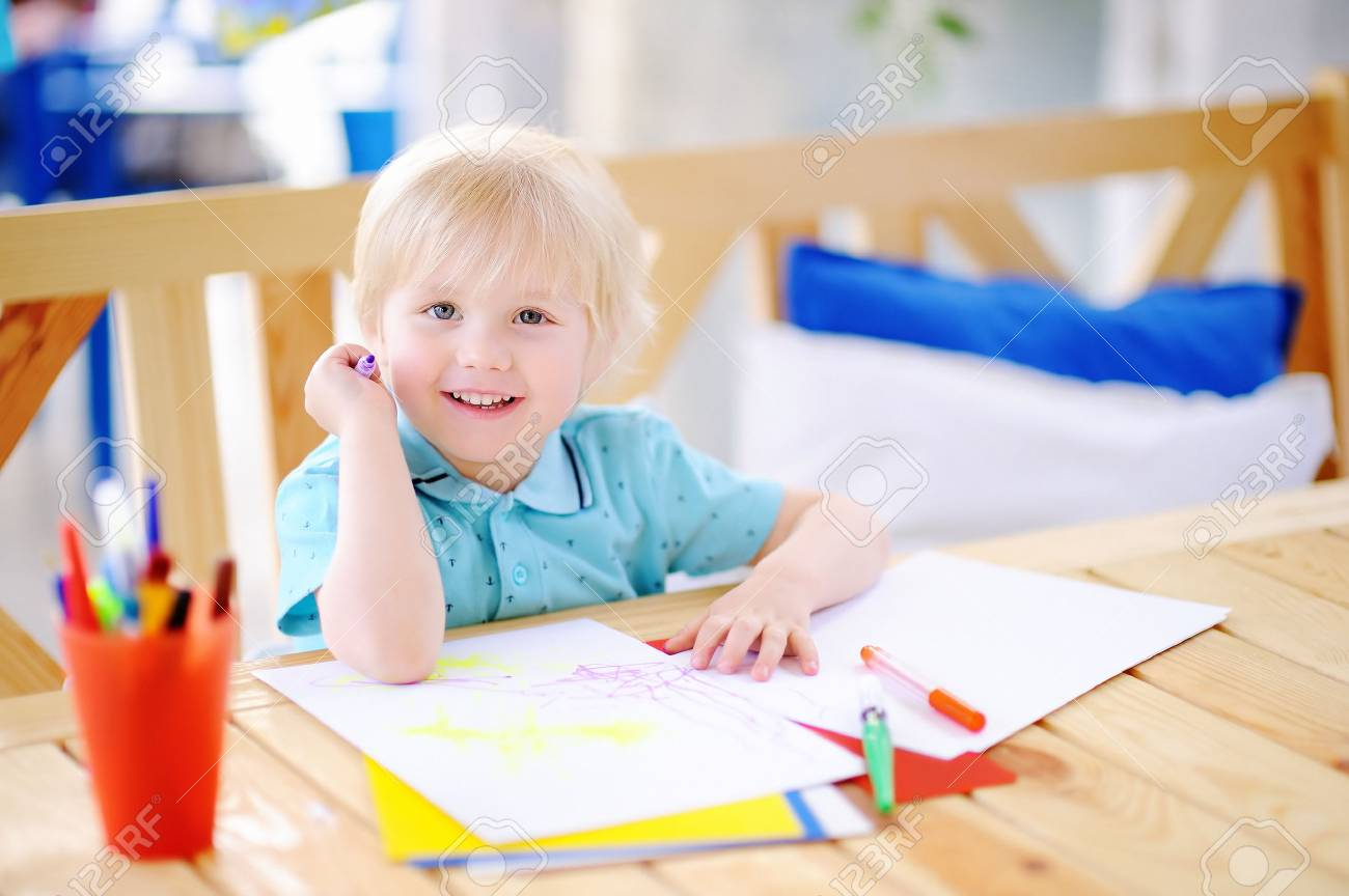Cute little boy drawing and painting with colorful markers pens at kindergarten. Creative kid painting at playschool. Development toys for preschooler children - 82937357