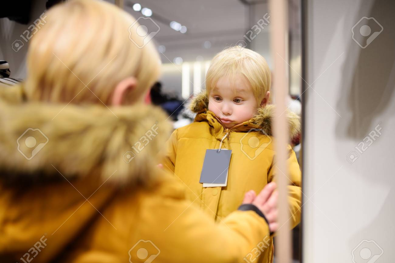 db181d41c Cute little boy trying new coat during shopping. Fashion warm clothes for  fall or winter