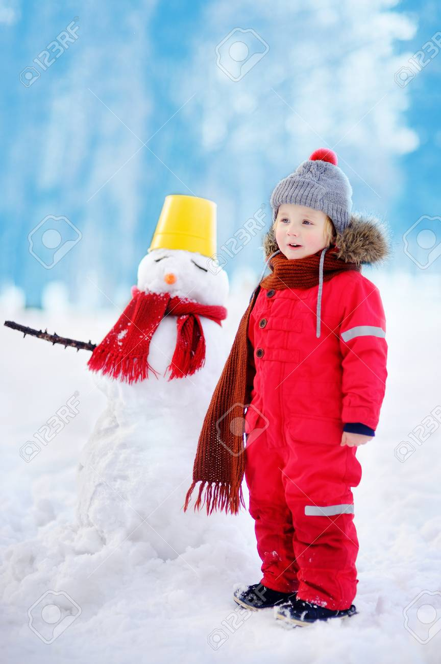 12ed45187 Little Boy In Red Winter Clothes Having Fun With Snowman. Active ...