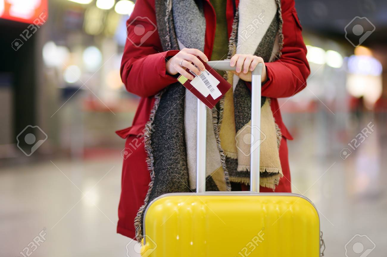 Close-up photo of woman with yellow suitcase holding passport and boarding pass at the international airport. Travel or immigration concept - 96552726