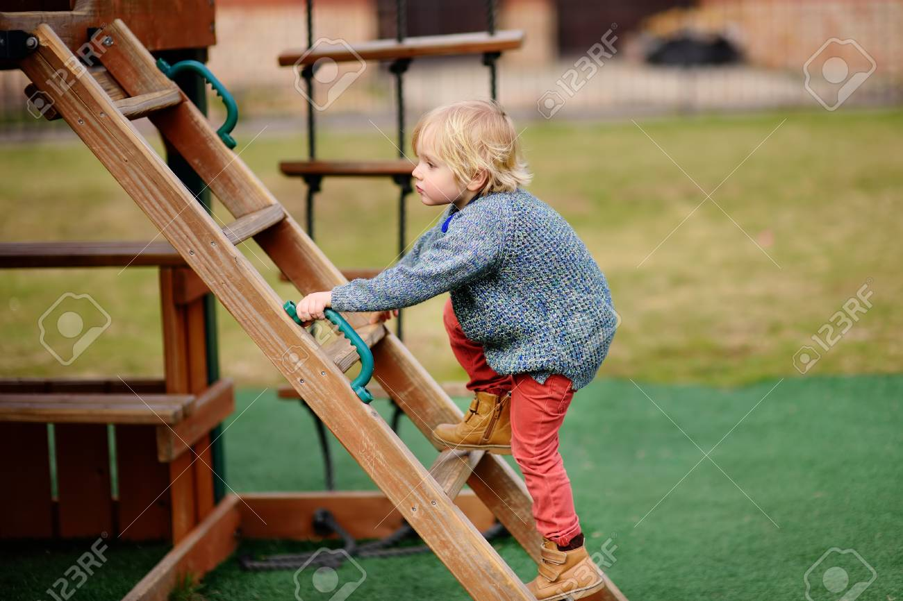 Cute little boy having fun on outdoor playground. Spring/summer/autumn active sport leisure for kids. Outdoors wooden equipment for children game - 103785337