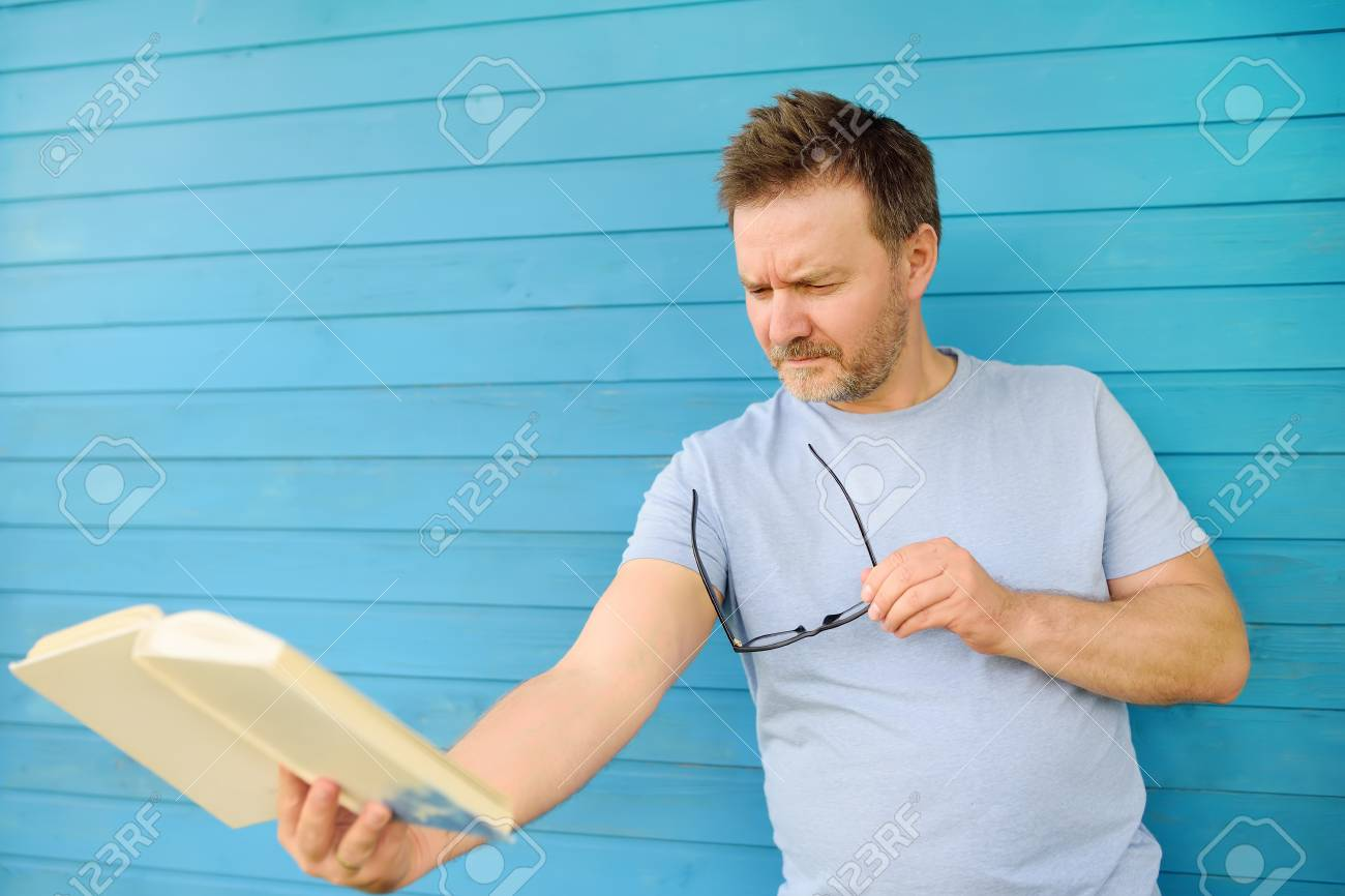 Portrait of mature man with big black eye glasses trying to read book but having difficulties seeing text because of vision problems. Hyperopia, presbyopia. - 112743551