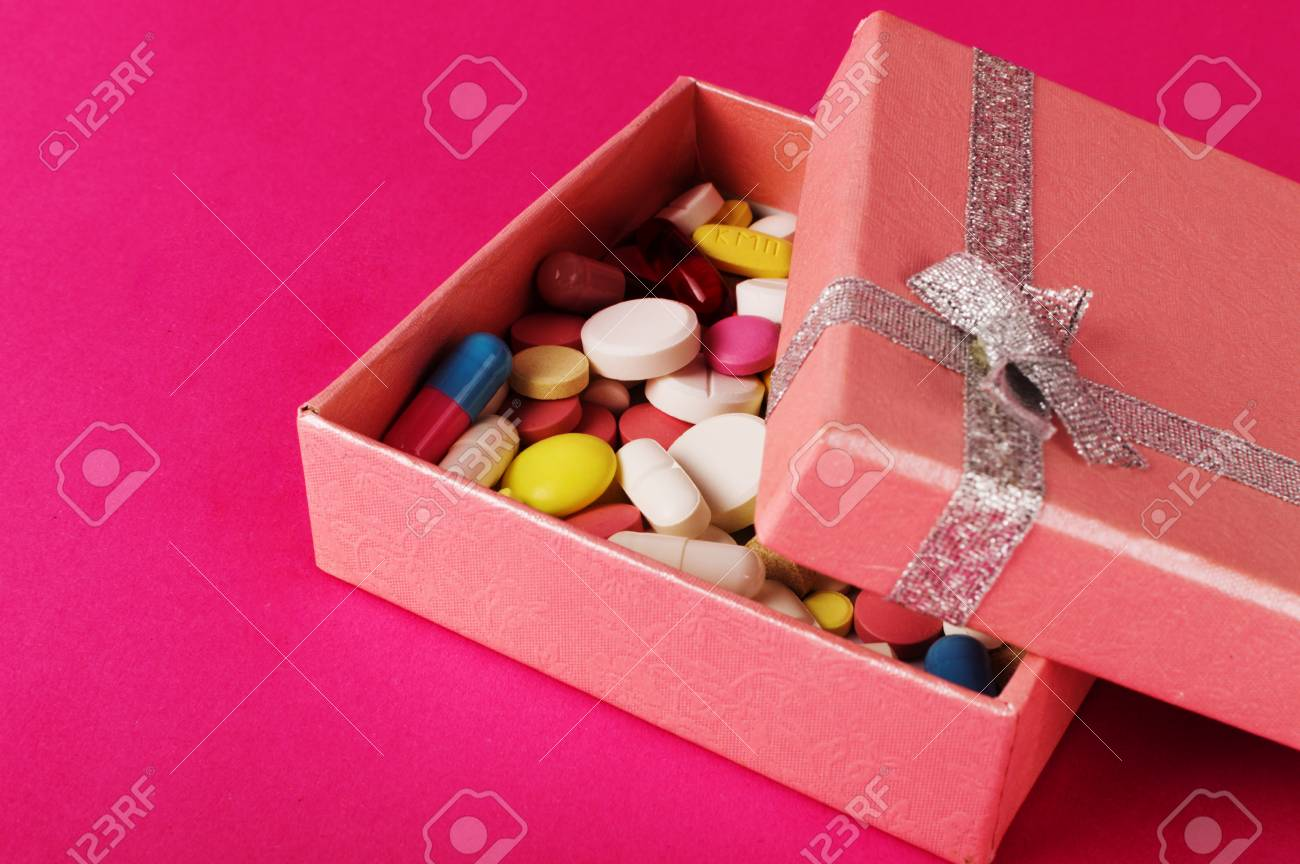 Gift box with pills on a pink backgroung. Medicine present concept. - 91832952