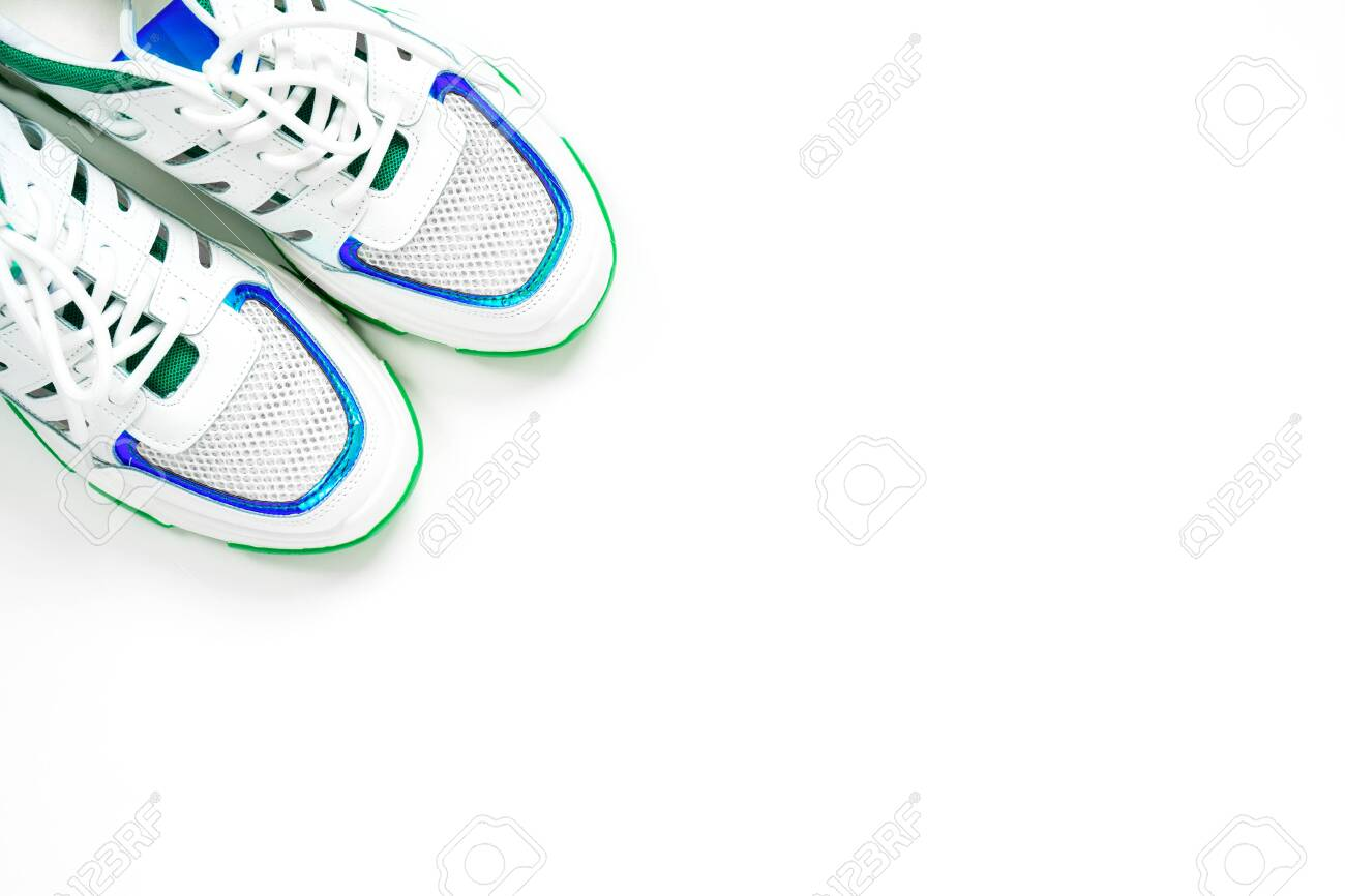 Clean stylish sneakers decorated with blue and green shiny lines stand in the corner of frame on white background, top view, copy space. Studio shot for new shoe advertising banner - 152544122
