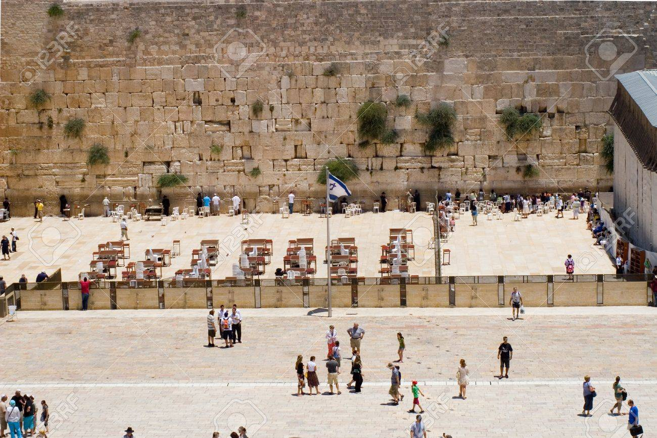 Western Wall, Jerusalem, Israel - July 17, 2009: People prays on male and female parts, people in area before, israel's flag wave. Stock Photo - 8780177