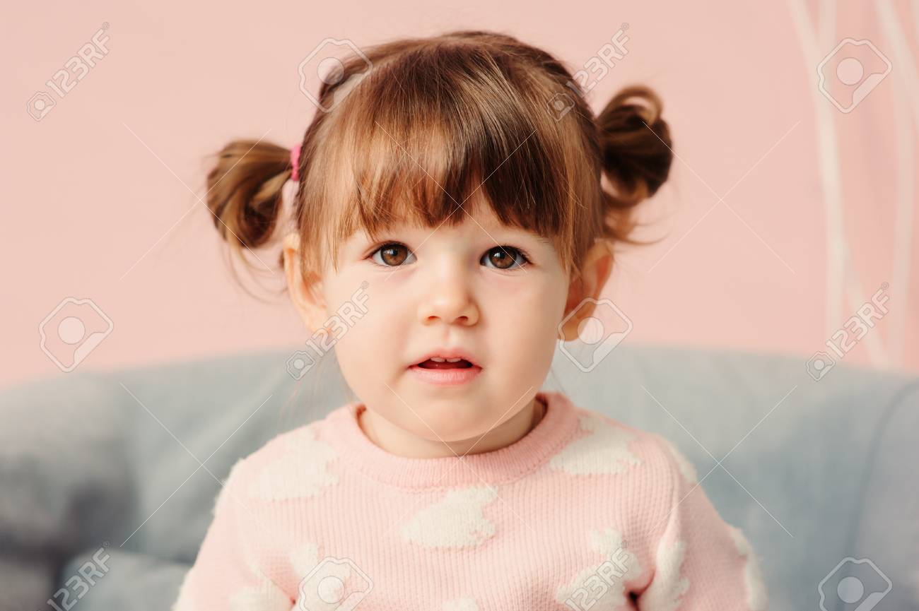 close up indoor portrait of cute happy 2 years old baby girl in pink  sweater Stock