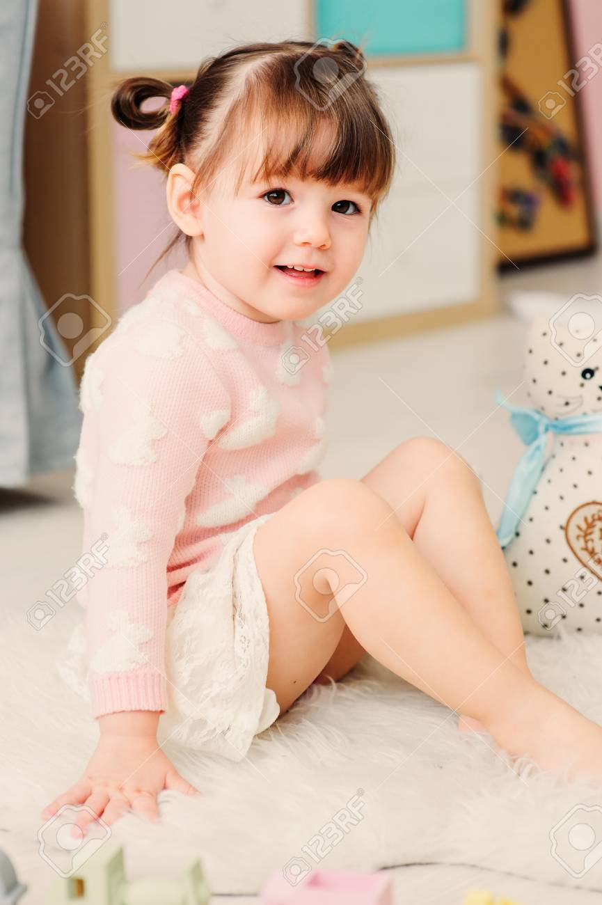 cute happy 2 years old baby girl playing with toys at home. Modern nursery  interior
