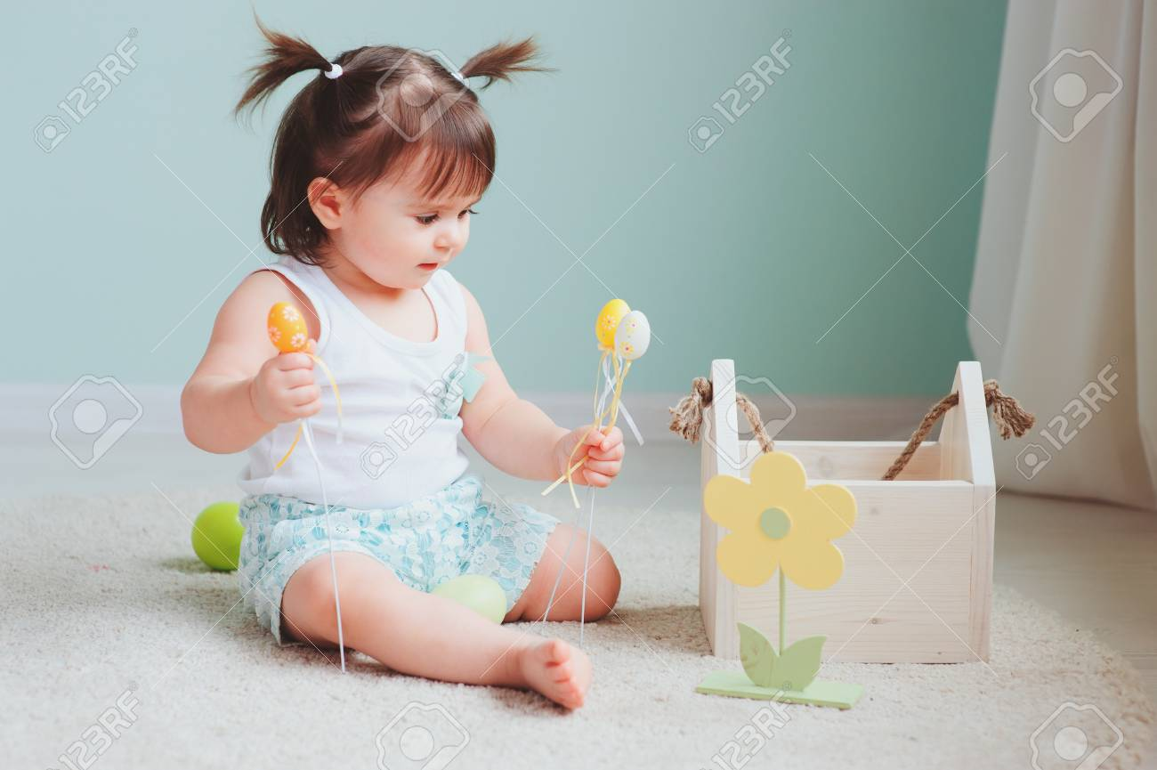 4e804a55978 close up indoor portrait of cute happy baby girl playing with easter  decorations Stock Photo -