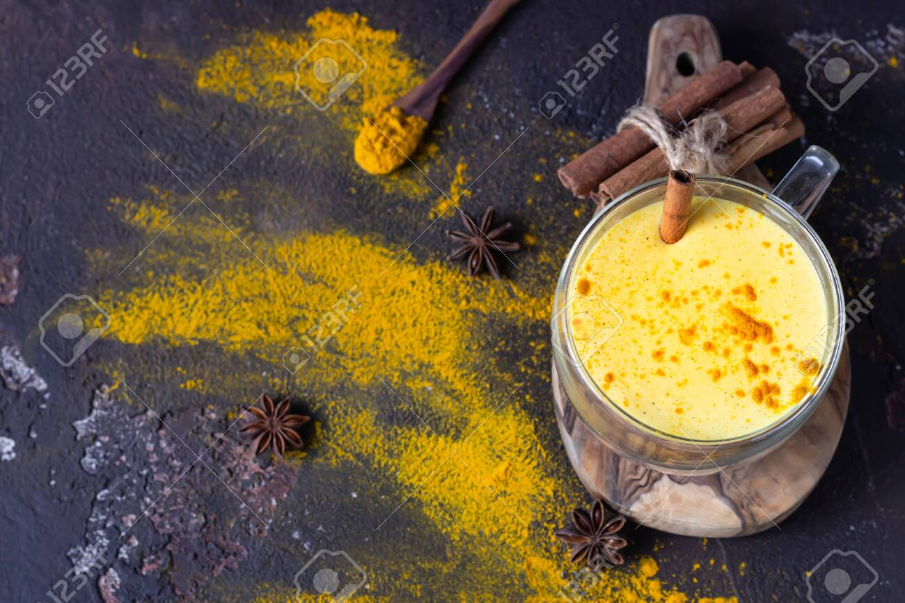 Golden milk or latte with turmeric (curcuma) powder with spices, dark brown concrete background. Trendy detox, immune boosting, anti-inflammatory healthy cozy drink. - 144021289
