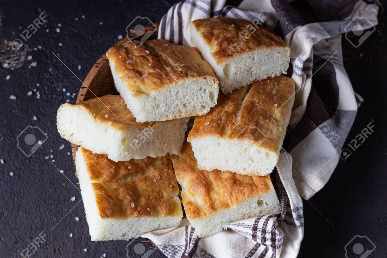 Traditional Italian focaccia bread with salt and olive oil. Homemade flat bread focaccia. Focaccia Genovese. - 144141216