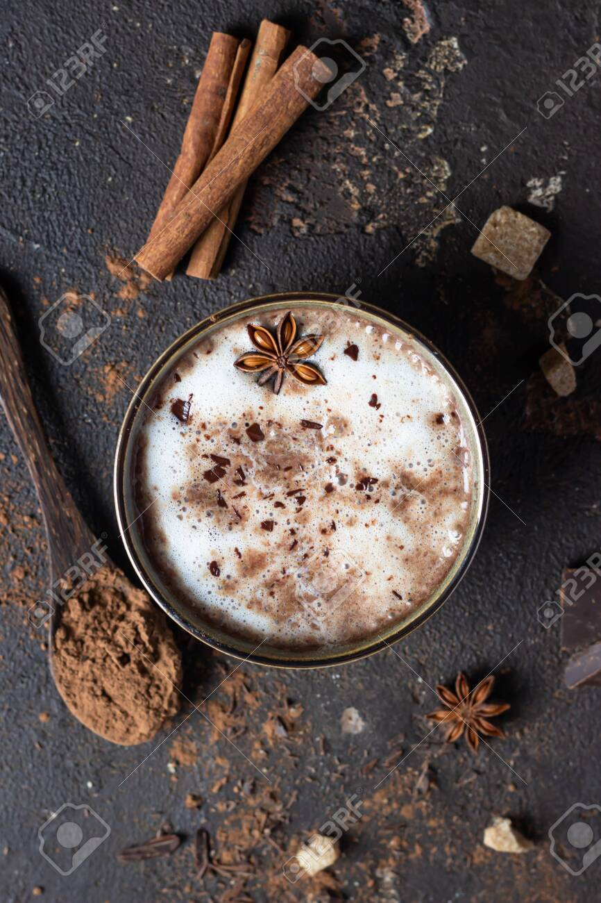 Cup of hot cocoa or hot chocolate with anise star and cinnamon sticks. Traditional beverage for autumn or winter time. Dark background. Top view. - 148871573