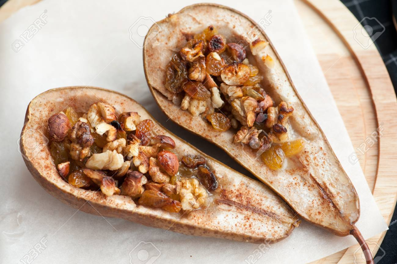 Dessert From The Baked Pears With Honey And Nuts In A Wooden