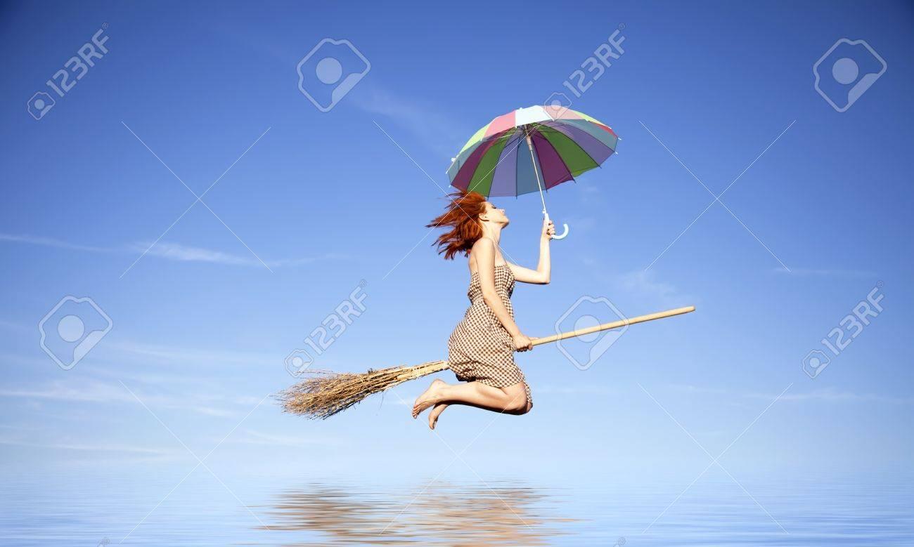 banque dimages jeunes rousse sorcire sur un balai volant dans le ciel avec un parapluie sur leau