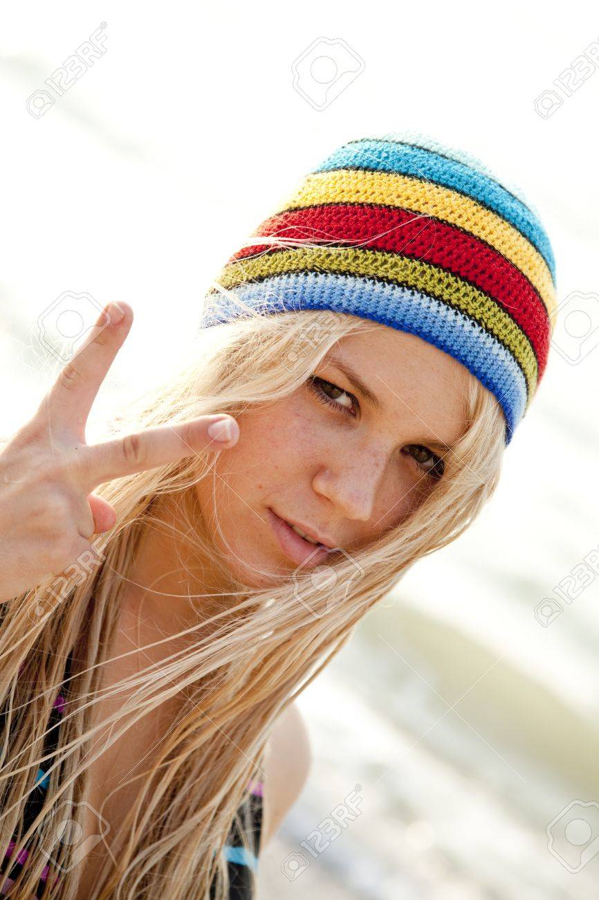 Beautiful young blonde girl in rastafarian hat show two fingers in V  symbol. Sunlight is 92b757435e60
