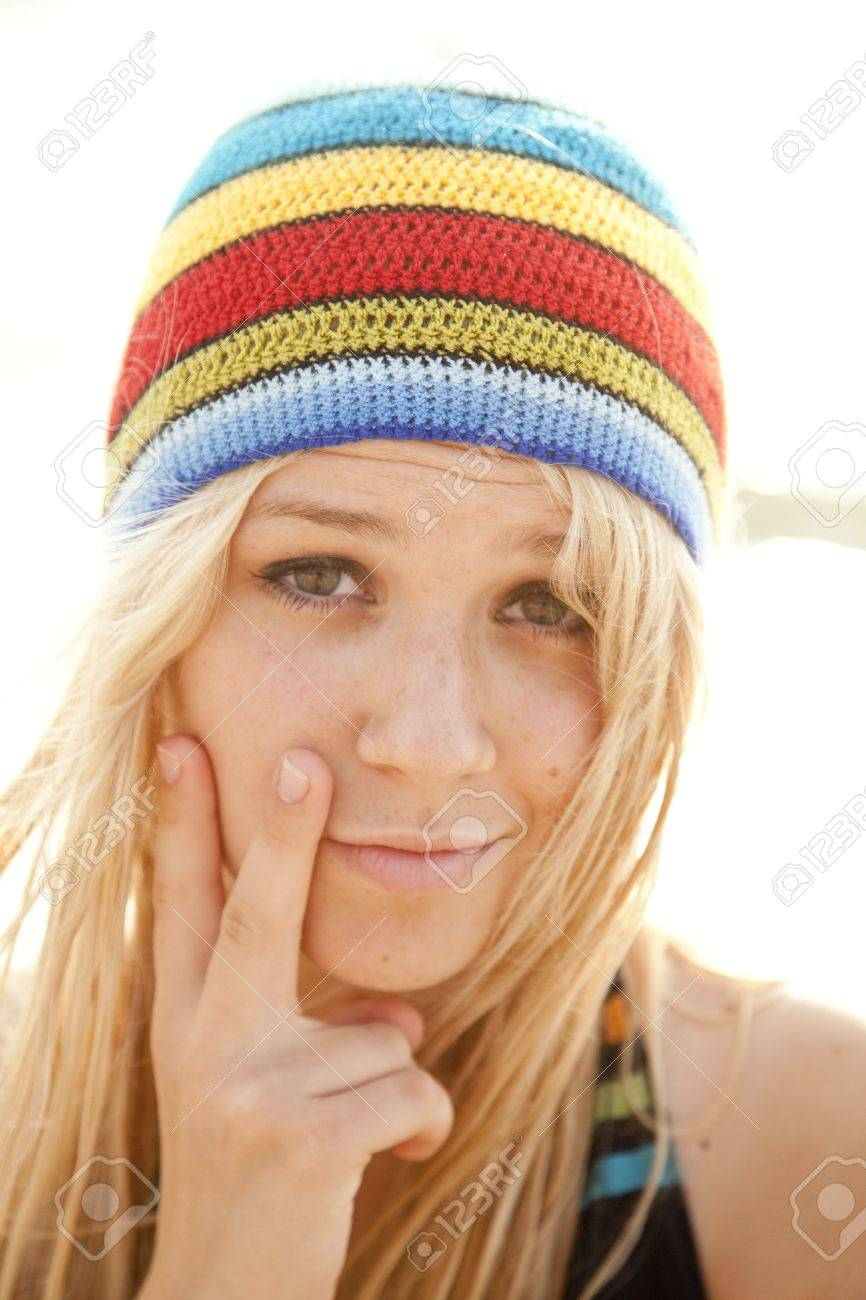 Beautiful young blonde girl in rastafarian hat. Sunlight is on background.  Stock Photo - 2cef2fc046a4