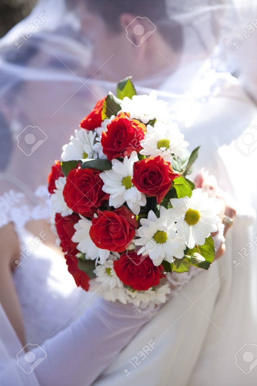 Bridegroom and bride kissing and holding beautiful red roses wedding flowers bouquet Stock Photo - 7690473