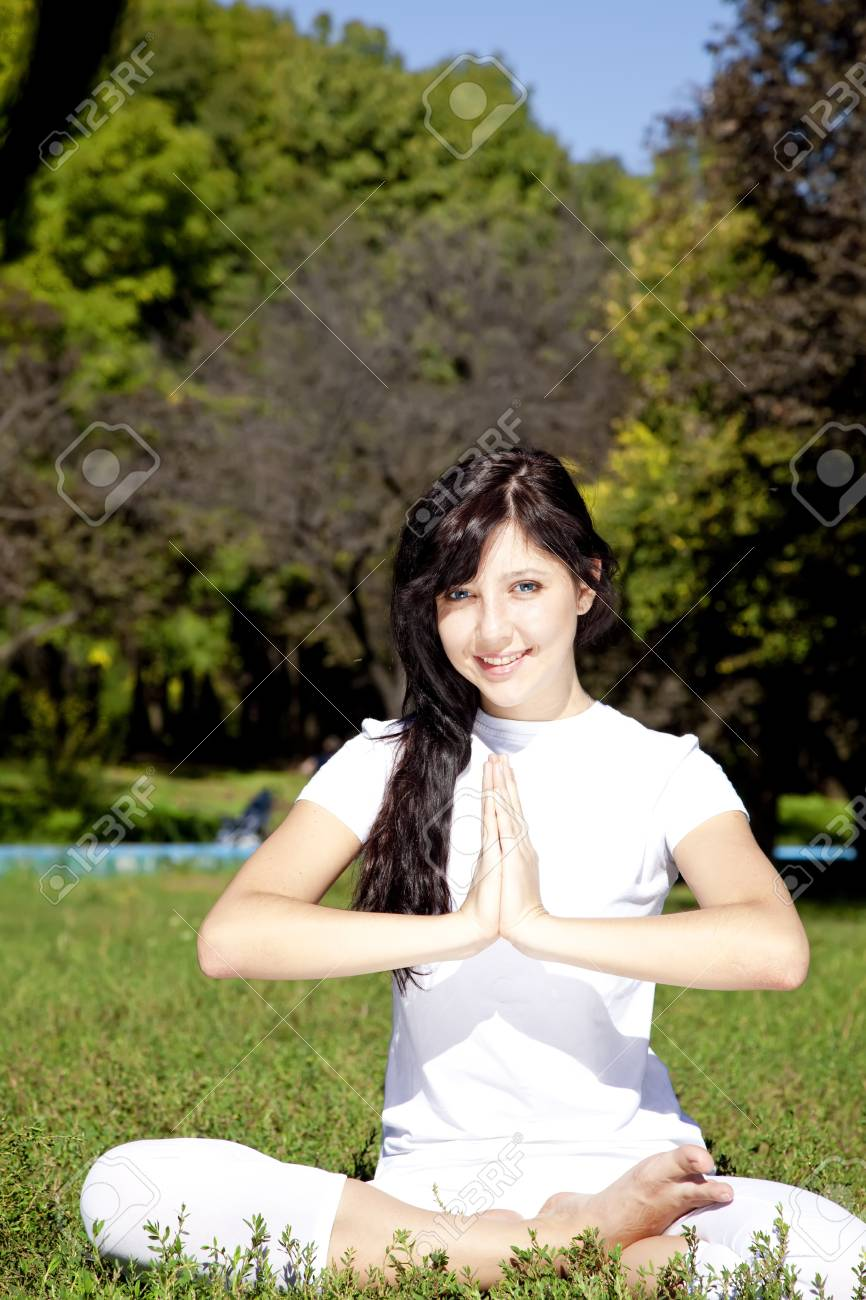 Beautiful young brunet yoga girl on green grass in park. Stock Photo - 7855744