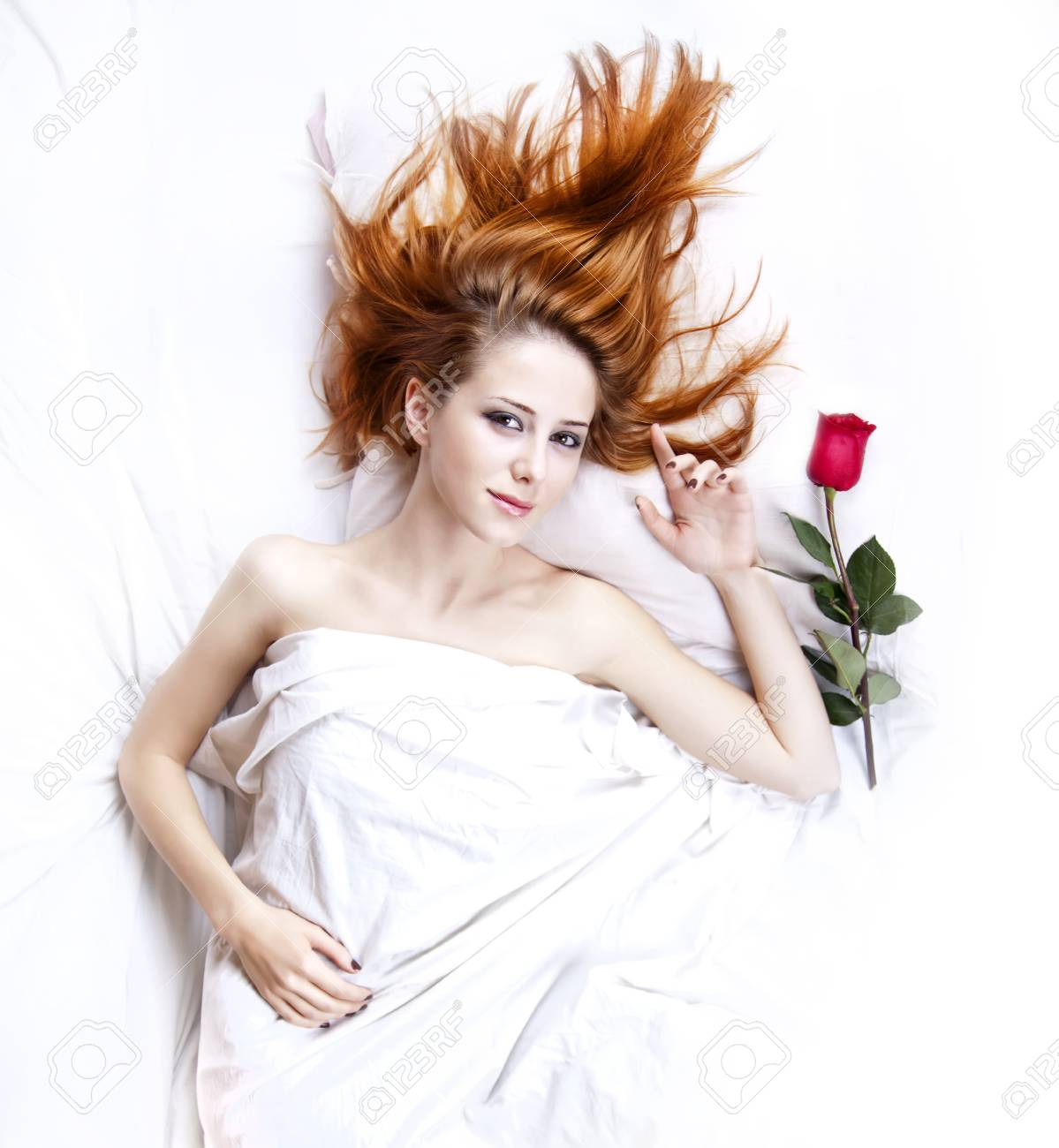 Fashion red-haired girl with rose in the bedroom. Studio shot from top. Stock Photo - 8207330