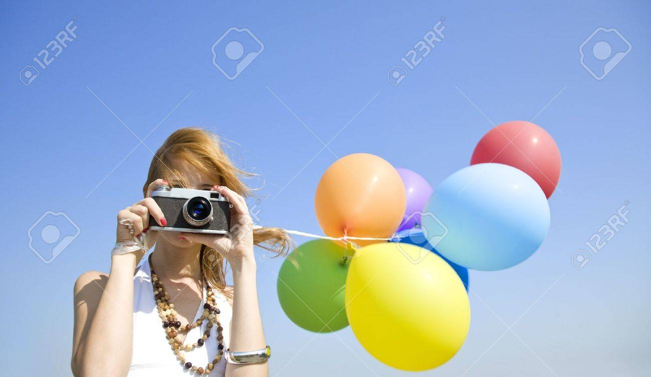 Redhead girl with colour balloons and camera at blue sky background. Stock Photo - 10690307