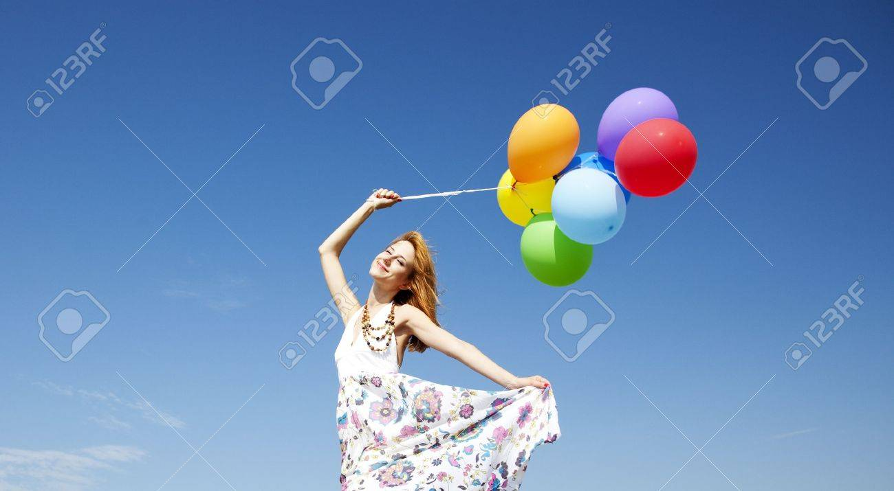 Redhead girl with colour balloons at blue sky background. Stock Photo - 10690174