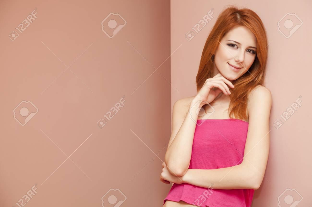 Beautiful redhead girl near wall. Stock Photo - 11670941