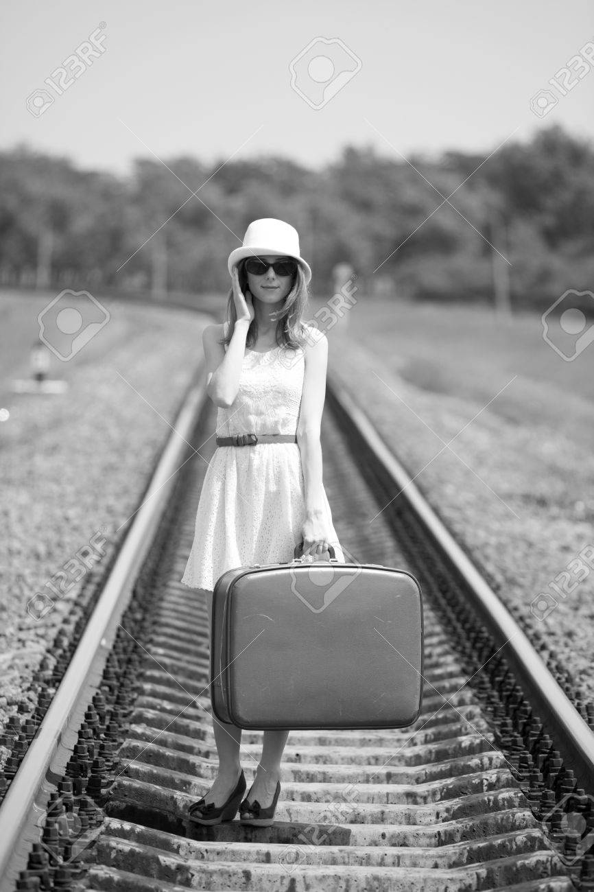 Young fashion girl with suitcase at railways. Photo in black and white style. Stock Photo - 13873468