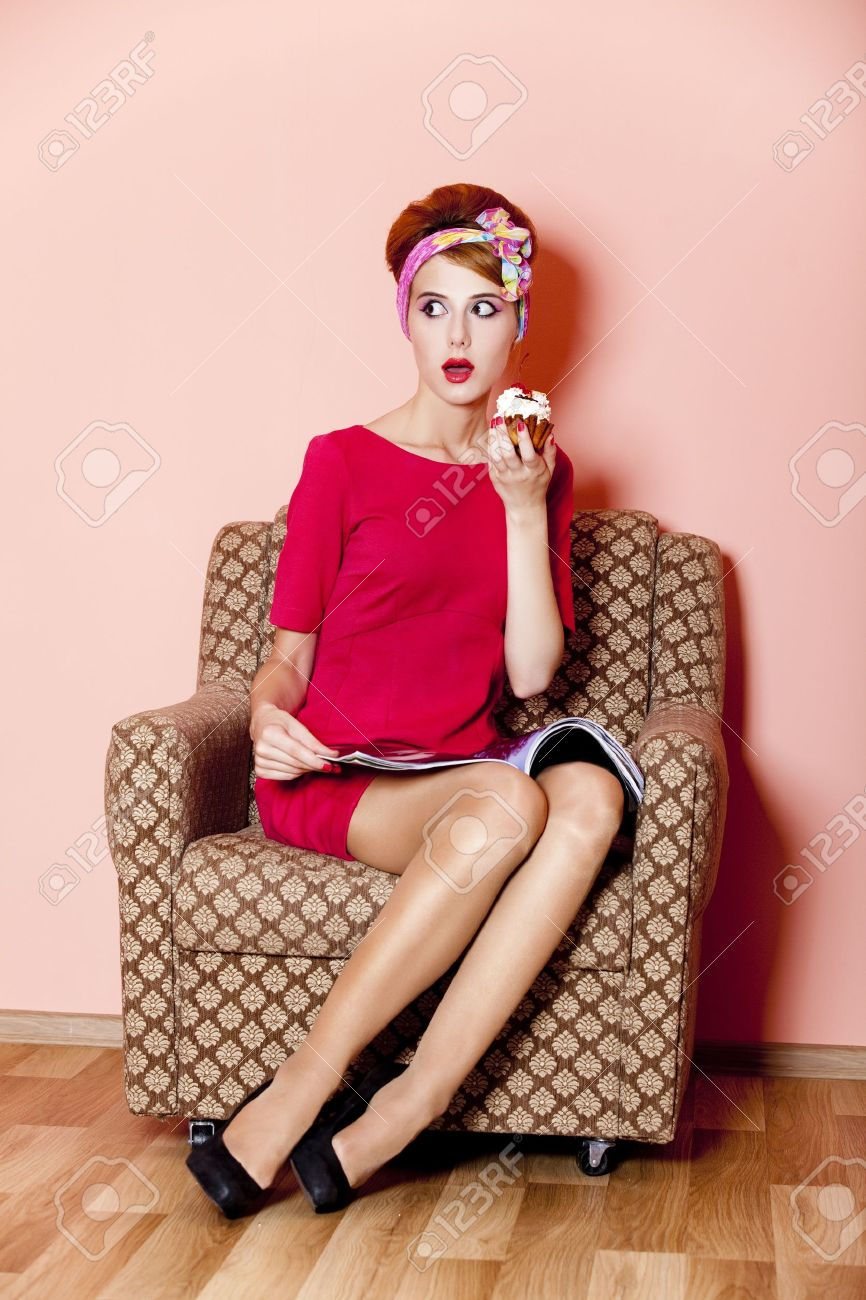 Style girl in red dress sitting in armchair with cake and magazine Stock Photo - 14545204