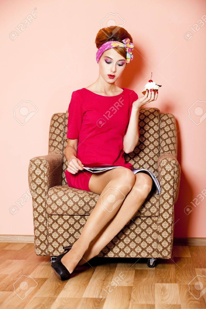 Style girl in red dress sitting in armchair with cake and magazine Stock Photo - 14545253