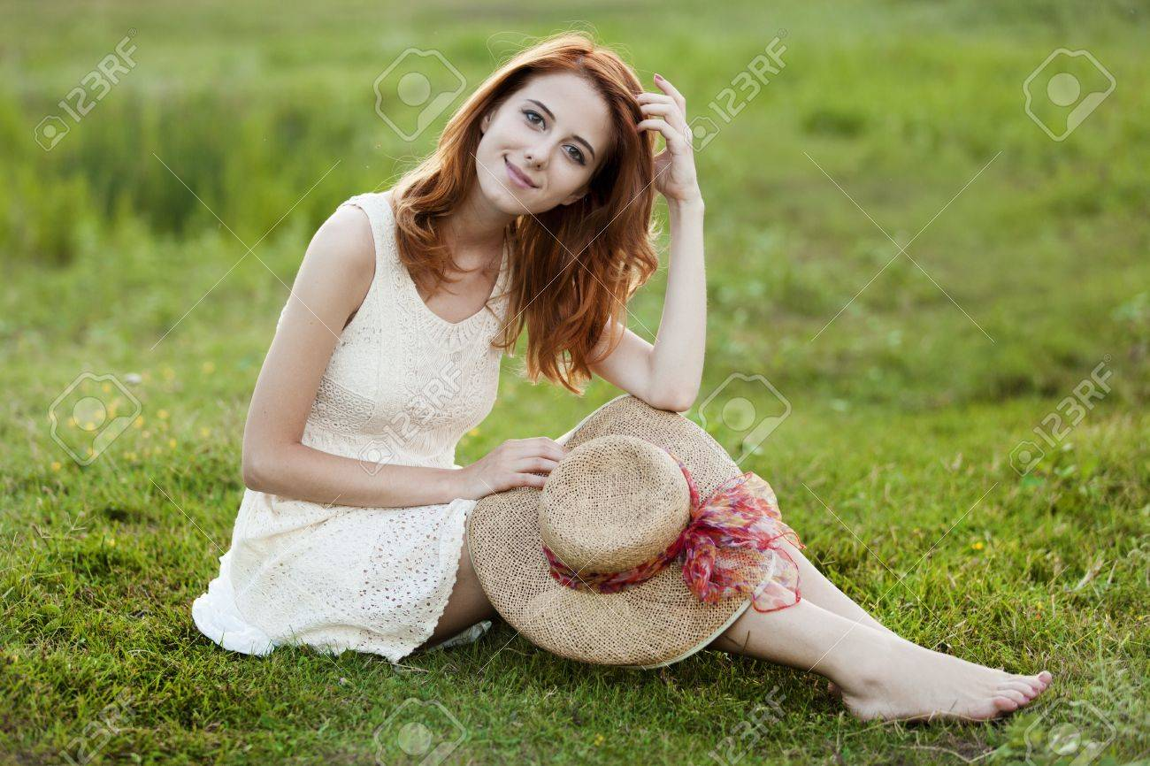 Redhead girl at green grass at village outdoor. Stock Photo - 14545235