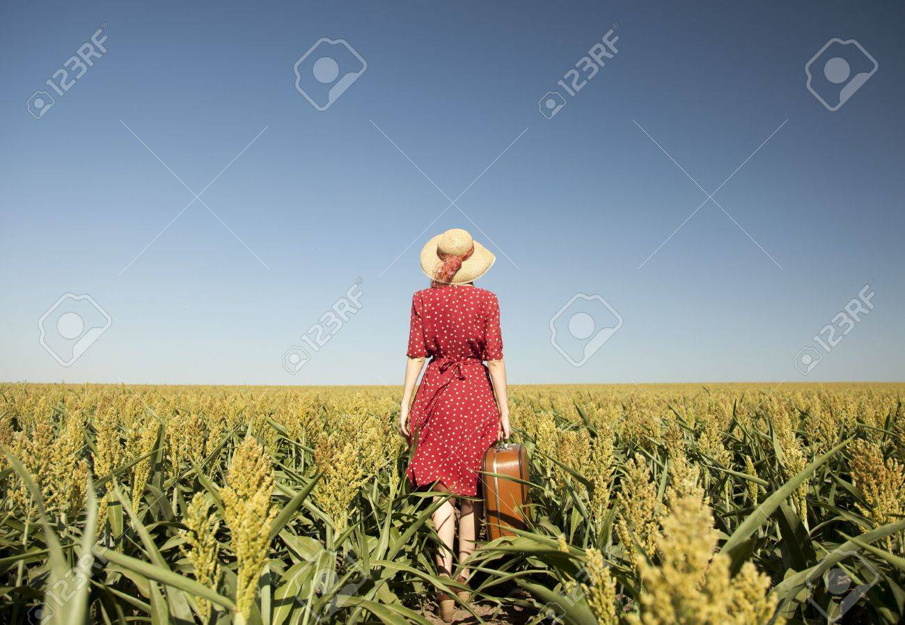 Redhead girl with suitcase at corn field. Stock Photo - 14544834