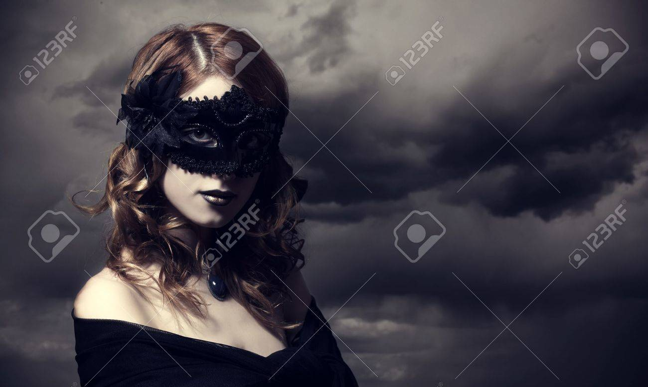 Enchantress in mask at storm sky background. Stock Photo - 16742377