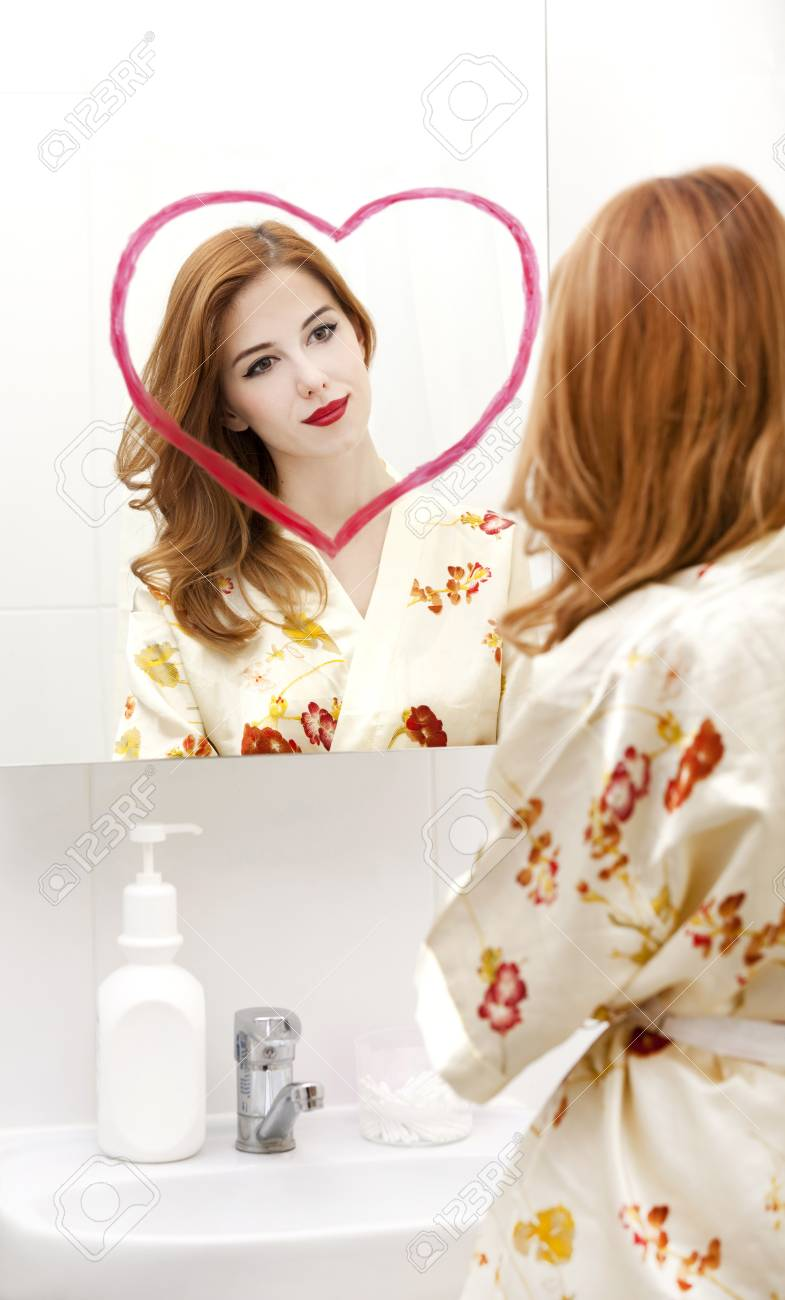 Redhead girl near mirror with heart it in bathroom. Stock Photo - 16824789